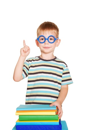 Little boy wearing glasses with books. A young elementary school student pointing a finger upward. Isolated on white background photo