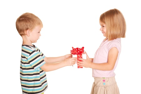 Little kids friendship and love. Little boy giving a little girl a gift. Present for a birthday, valentine's day or other holiday. Isolated on white background photo