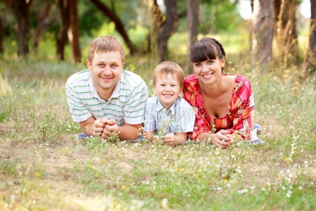 Father, mother and son on the grass. Summer holiday. Happy family outdoors. photo