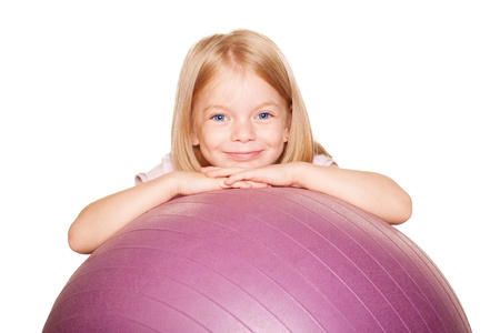Pretty little girl with a fitness ball. Isolated on white background photo