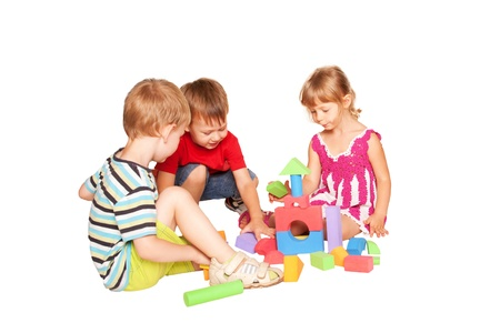 baby blocks: Three children playing and building a tower of blocks together. Isolated on white background.