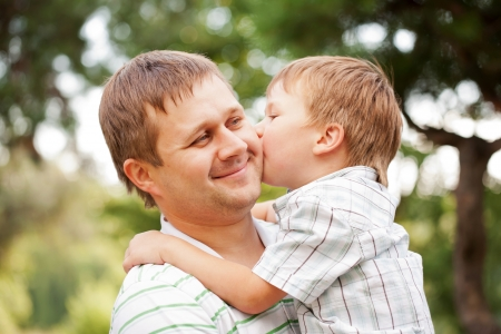 Happy father and son outdoors. Child kissing daddy. photo