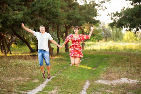 Happy middle-aged couple jumping outdoors. Summer holiday. photo