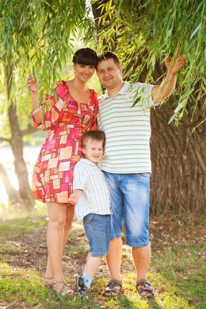 mom kiss son: Father, mother and son in the park. Summer holiday. Happy family outdoors. Stock Photo