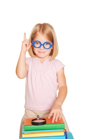 Little girl wearing glasses with books and magnifying glass pointing index finger up. Isolated on white background photo