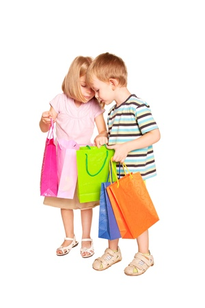 ni�os de compras: Ni�os de compras. Pareja joven, ni�o y ni�a, comprobar y mirar bolsas de la compra. Aislado sobre fondo blanco.