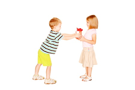 Little childrens love. Little boy giving to little girl the gift. Present for birthday, valentine's day or other holiday. Isolated on white background photo