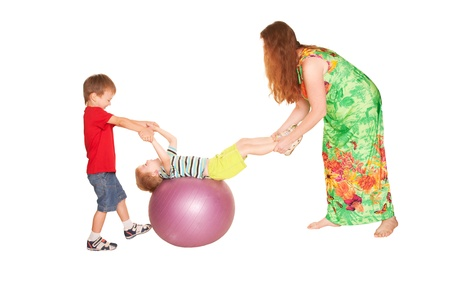 The mother and brother doing exercises on fitness ball for a little boy. Family fitness. Isolated on white background photo