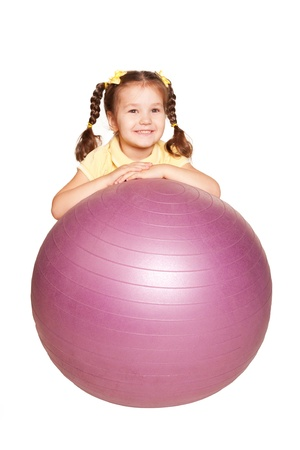 aerobic treatment: Smiling little girl with pigtails and fitness ball. Isolated on white background