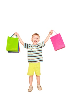 Happy little boy with shopping bags. Isolated on white background photo