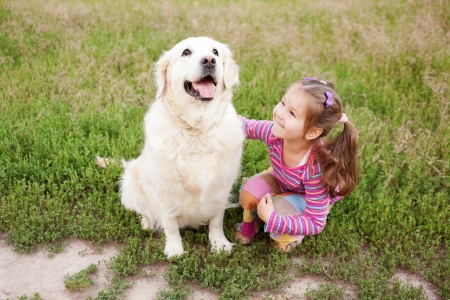 Happy little girl hugging a dog breed golden retriever on green grass in the park. Stock Photo