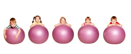 Merry group of five children playing sports. Little boys and girls with fitness balls. Physical exercises in the fitness center. Isolated on white background. Standard-Bild