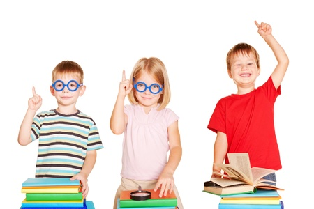 Happy group of children in a classroom with books. Kids showing up at something. Isolated on white background. photo