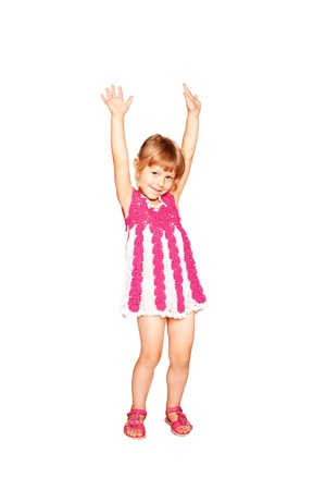 Happy little girl in a knitted dress dancing. Isolated on white background photo