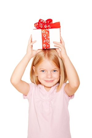 Pretty little girl with gift on head. Festive concept. Isolated on white background photo