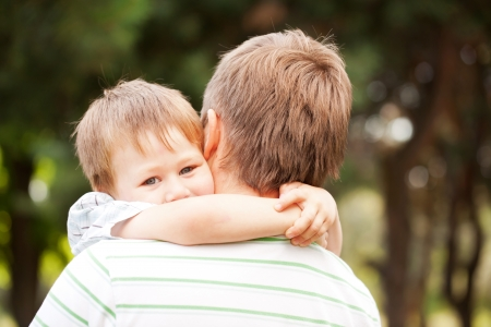 Happy father and son outdoors.  Child hugging daddy. Stock Photo