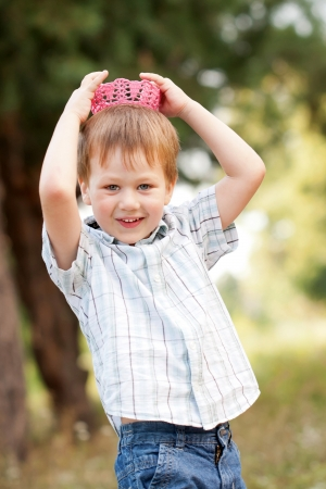 A boy wearing a knitted crown on the head. photo