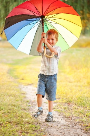 Adorable boy with colorful umbrella in the park photo