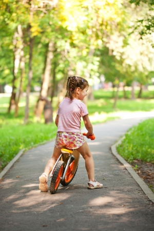 Little girl riding a bike on a sunny day. Rear view. photo