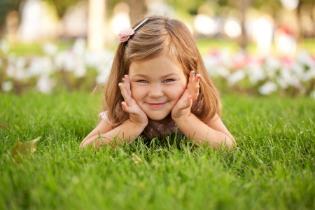 family park: Happy beautiful little girl lying on the grass on the lawn. Her nails have a colorful manicure.