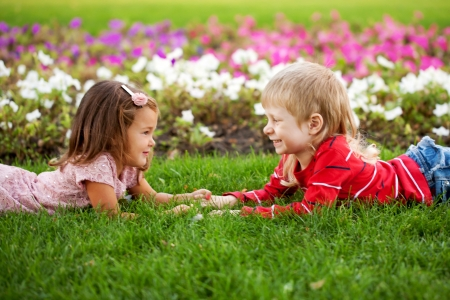 Love concept. Couple of kids, little boy and girl lying on the grass, holding hands and looking eye to eye. photo