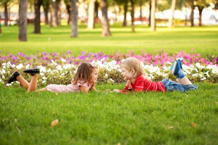 Love concept. Couple of kids, little boy and girl lying on the grass, holding hands and looking eye to eye.