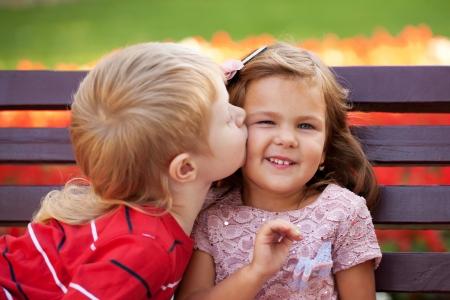 amistad: Concepto del amor. Un par de niños cariñosos entre sí abrazos y besos.