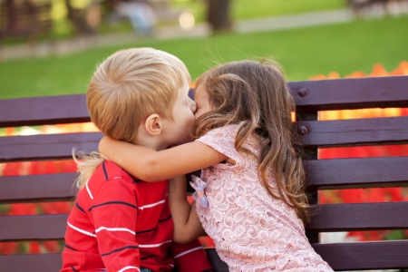 hugs and kisses: Love concept. Couple of kids loving each other hugging and kissing. Stock Photo