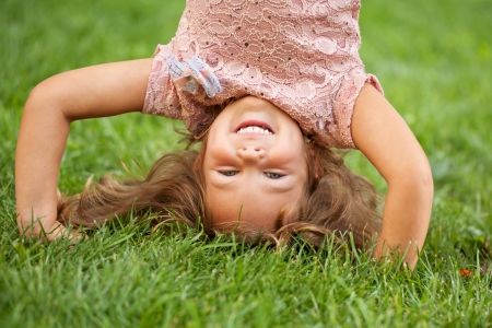 Funny happy little girl standing on her head on the grass in the park. photo