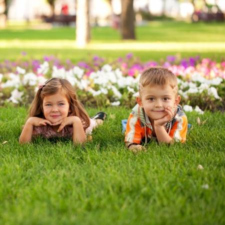 男の子と女の子の花の中で草でリラックス。