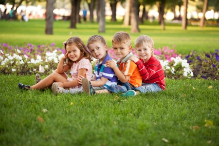 brothers and sisters: A group of children relaxing and playing in the park on the green grass.