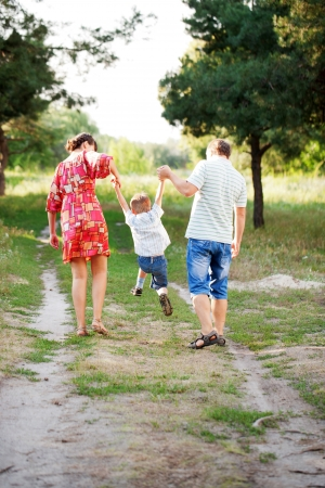 Happy family concept. Father, mother and son walking outdoors.  Rear view. Summer holiday.  photo