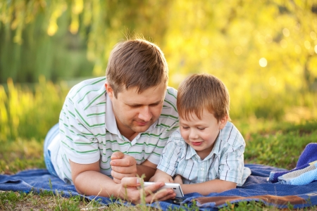 Father and son playing with smartphone  together outdoors