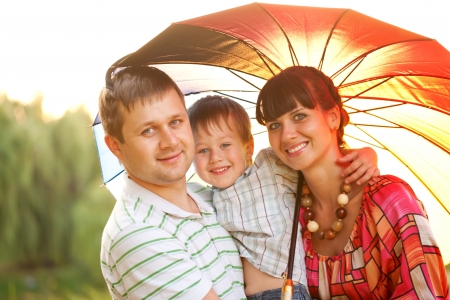 Happy family concept. Father, mother and son in the park with colorful umbrella. photo