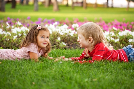 Friendship concept. Couple of kids, little boy and girl lying on the grass, holding hands and talking. The tender feelings. photo