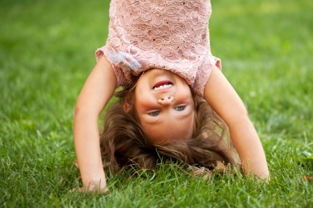 Happy little girl standing on her head on the grass in the park. Childhood concept. Summer holiday. photo