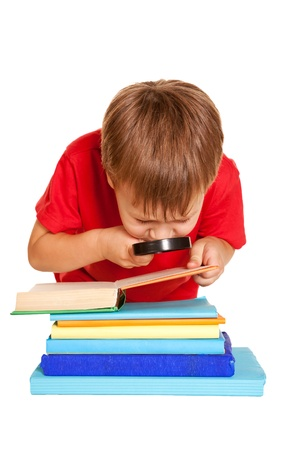 poor eyesight: Little boy wearing glasses reading a book with a magnifying glass. Poor eyesight. Isolated on white background.