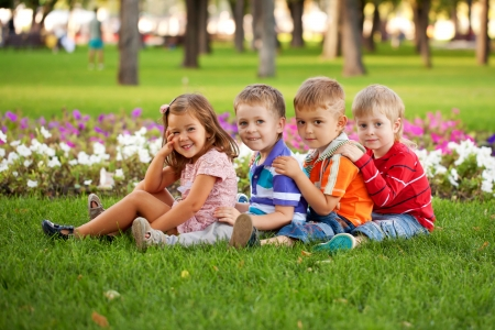 Group of fun children relaxing and playing in the park on the green grass. photo