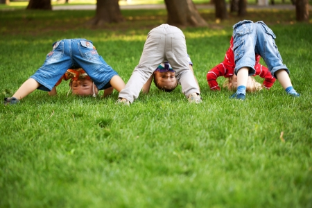 Three little boys turning somersaults,  doing upside down and playing on green grass