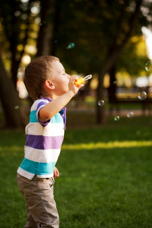 Little boy playing with soap bubbles in the park photo