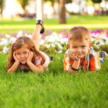 among: Little boy and girl relaxing on the grass among flowers