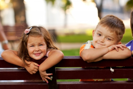 Little boy and girl on a bench in the park