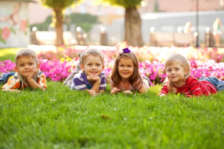 A group of little children relaxing and playing in the park on the green grass  photo