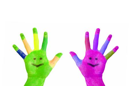caritas pintadas: Dos Manos pintadas de colores con caras sonrientes en las palmas de las manos y los dedos levantados aislados sobre fondo blanco