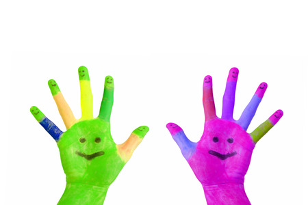 Two painted colorful hands with smiling faces on the palms and fingers raised up  Isolated on white background Stock Photo