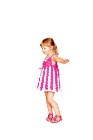 Happy little girl in knitted pink dress dancing. Isolated on white background photo