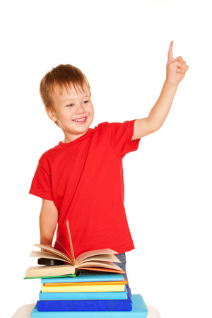 Little boy with books. Student pointing a finger upward, ready for your text or symbols. Isolated on white background photo