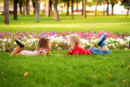 Love concept.Couple of children, little boy and girl lying on the grass, holding hands and looking eye to eye. photo