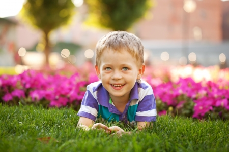 Adorable little boy lying among the flowers. Summer holiday. photo