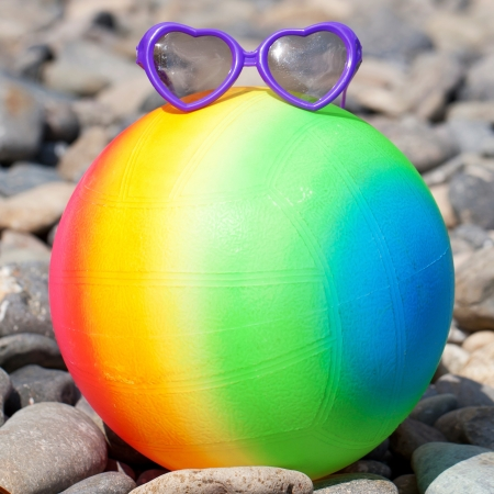 Summer holidays concept. Rainbow colorful beach ball with sunglasses on the pebbles. photo